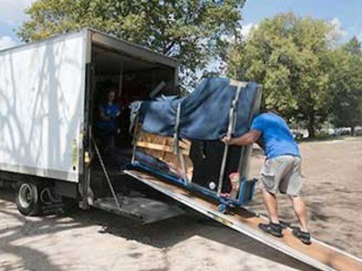2 removalists moving piano onto truck